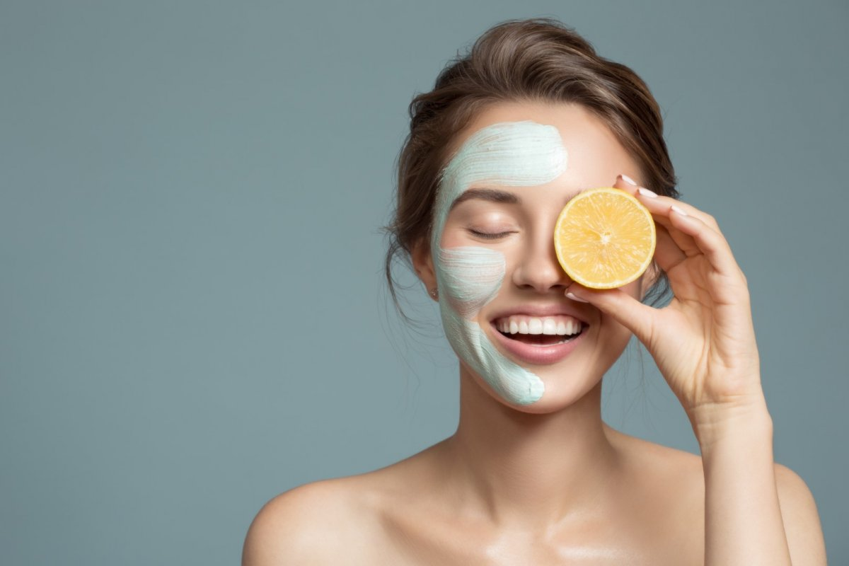 portret ładnej kobiety trzymajacej połówke pomaranczy przy oku z maseczka na drugiej stronie twarzy