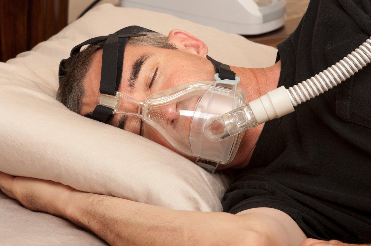 mężczyzna śpiacy z urządzeniem do leczenia bezdechu sennego