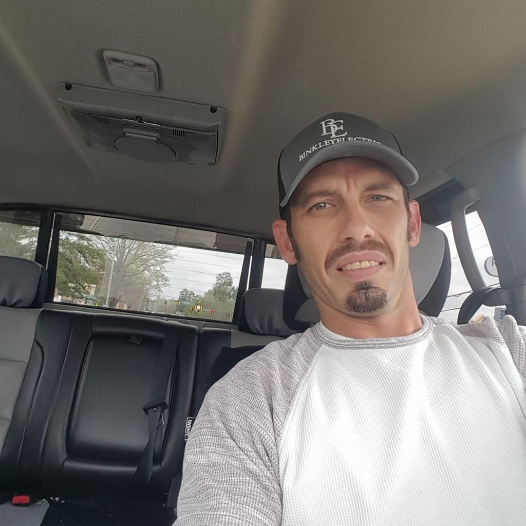 mężczyzna w czapce z daszkiem siedzi w samochodzie na miejscu kierowcy