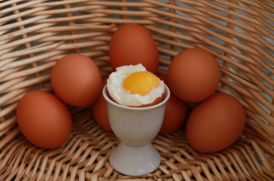 jajko na miękko na tle innych całych jajek i wikliny