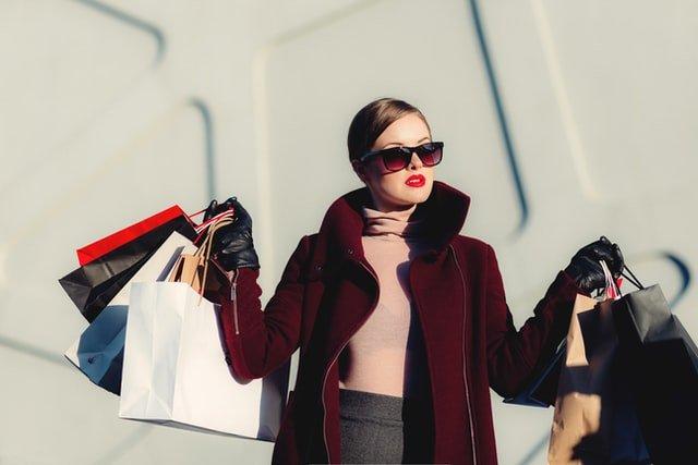kobieta w spiętych włosach i okularach przeciwsłonecznych trzyma torby w dłoniach