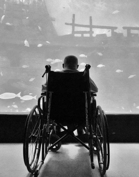 mężczyzna na tle dużego akwarium siedzi na wózku inwalidzkim