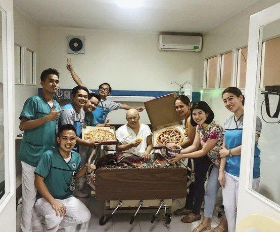 mężczyzna z zespołem downa na szpitalnym łóżku w towarzystwie lekarzy