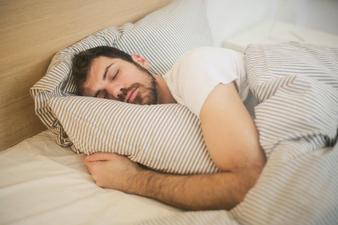 Mężczyzna śpiący w łóżku