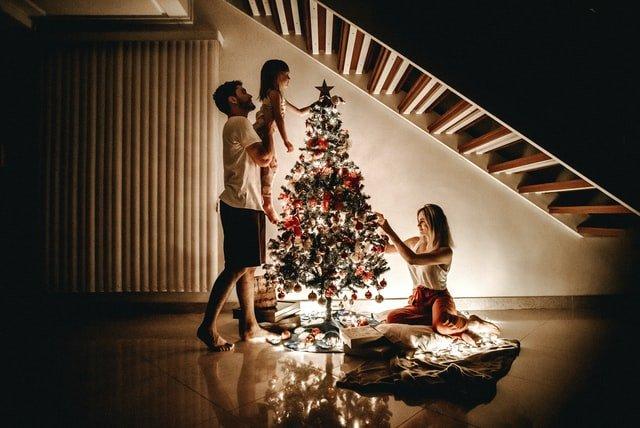 rodzina ubiera choinkę a mężczyzna podnosi dziewczynkę, żeby położyła coś na czubku drzewka