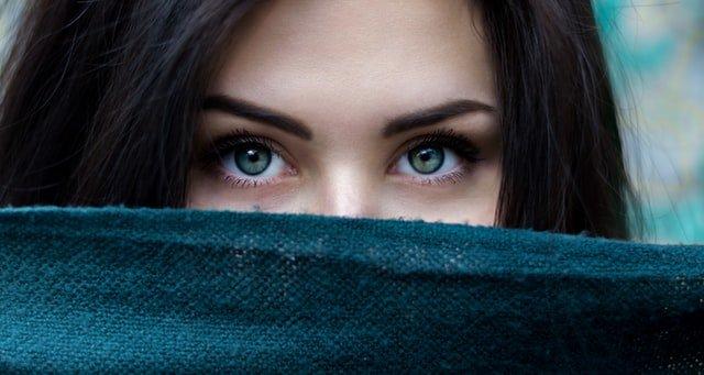 zbliżenie na zielone oczy brunetki, która zasłania sobie twarz swetrem