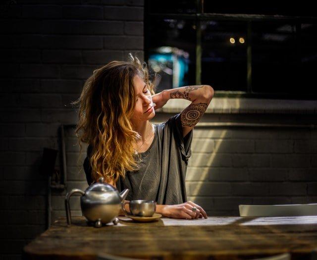 blondynka w rozczochranych włosach siedzi za stołem i łapie się za szyję