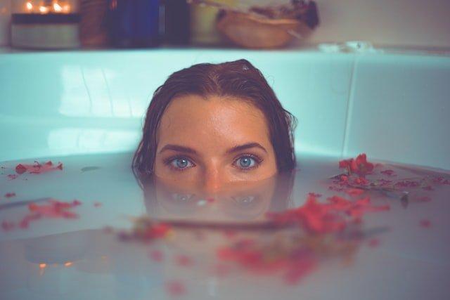 kobieta zanurza w połowie twarz w wodzie w wannie
