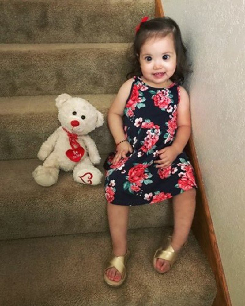 dziewczynka kilkuletnia w kwiecistej sukience siedzi na schodach