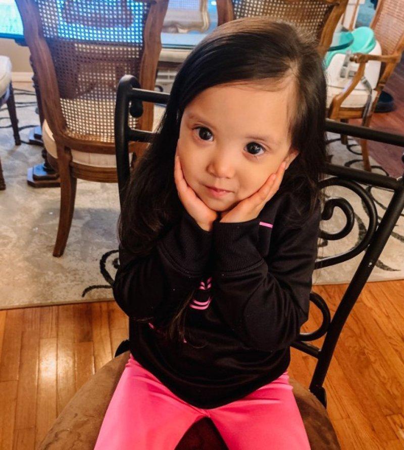 dziewczynka z dużymi oczami i długimi włosami patrzy w obiektyw siedząc na krzesełku