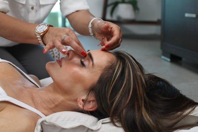 kobieta masuje nos innej kobiecie, która leży na leżance