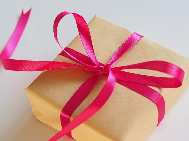prezent w beżowym papierze i różowej kokardzie
