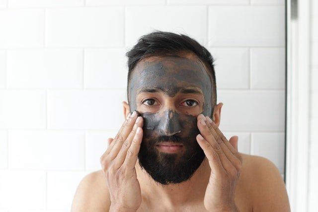 mężczyzna z brodą wmasowuje szarą maseczkę w twarz