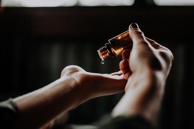 dłoń nalewa na drugą dłoń olejek