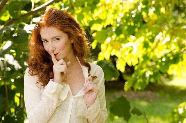 uśmiechnięta rudowłosa dziewczyna przykłada palec do ust i stoi na tle drzew