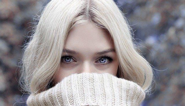 zbliżenie na niebieskie oczy blondynki, która zasłania beżowym swetrem twarz