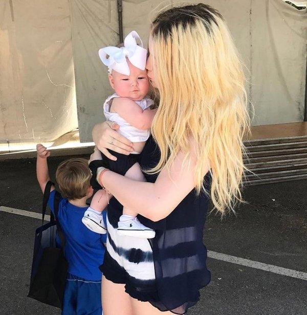 blondynka z długimi włosami trzyma w ramionach dziecko z kokardą białą na głowie
