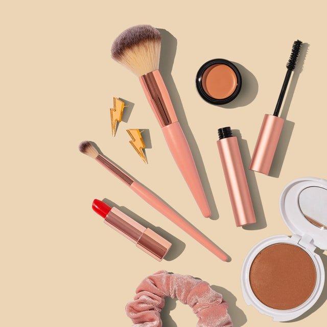 przybory do makijażu rozłożone na różowym tle