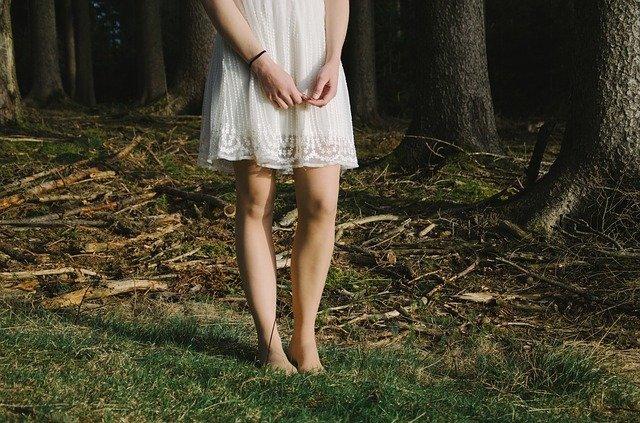 zdjęcie od pasa w dół kobiecej sylwetki ubranej w białą krótką sukienkę na tle lasu