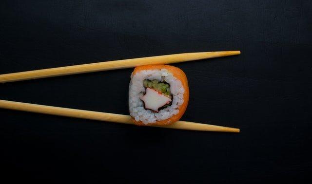 jedno sushi złapane miedzy dwie drewniane pałeczki