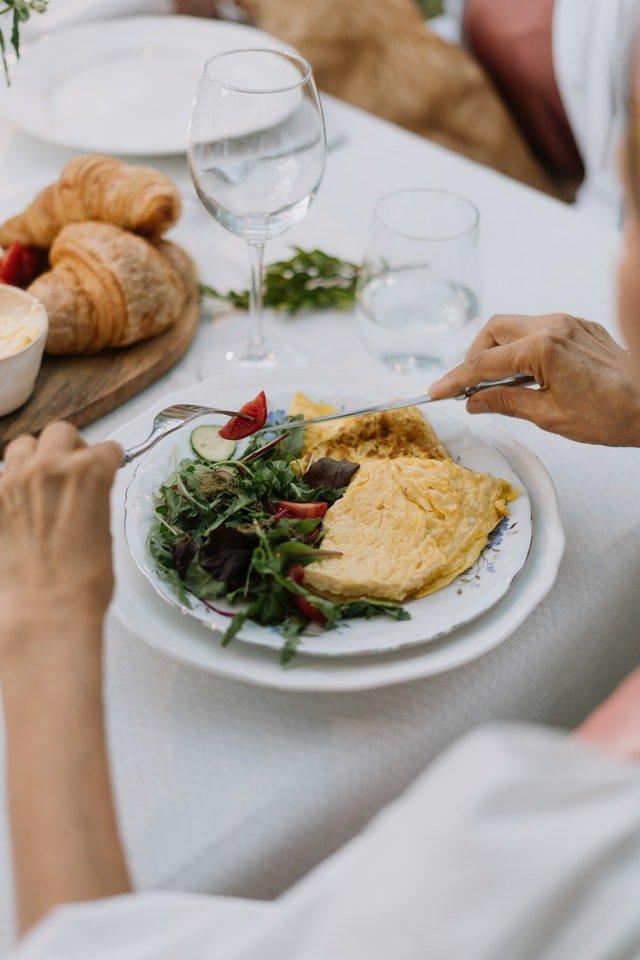 omlet z zieloną sałatą na białym talerzu na białym stole obok kieliszka