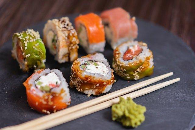 sushi ułożone na szarej desce obok drewnianych pałeczek