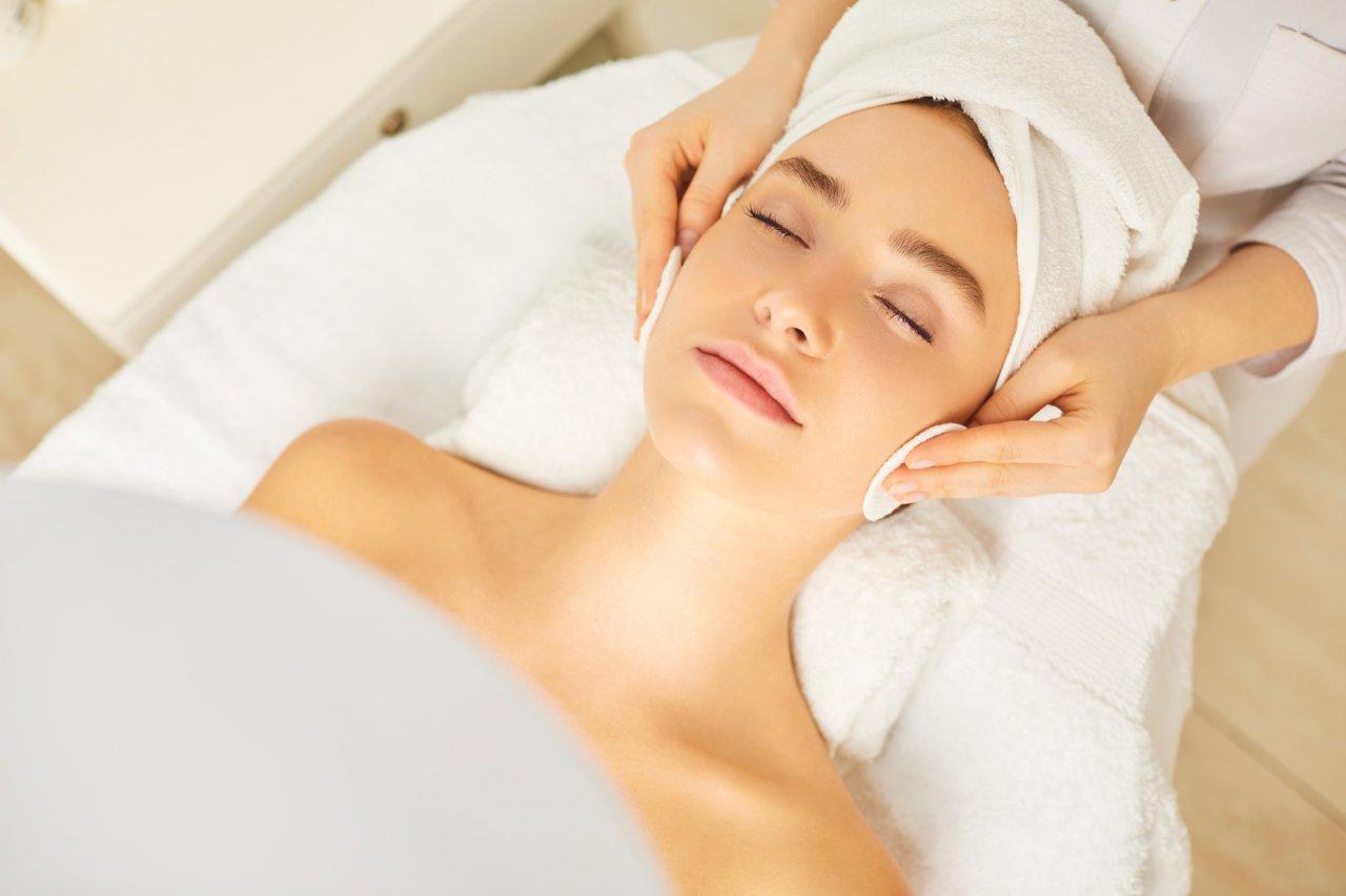 kobieta w turbanie z ręcznika leży na plecach z zamkniętymi oczami