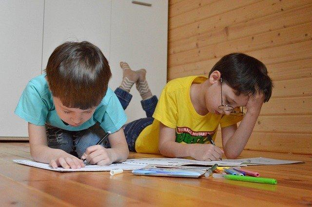dwóch chłopców leży na podłodze i czyta książki