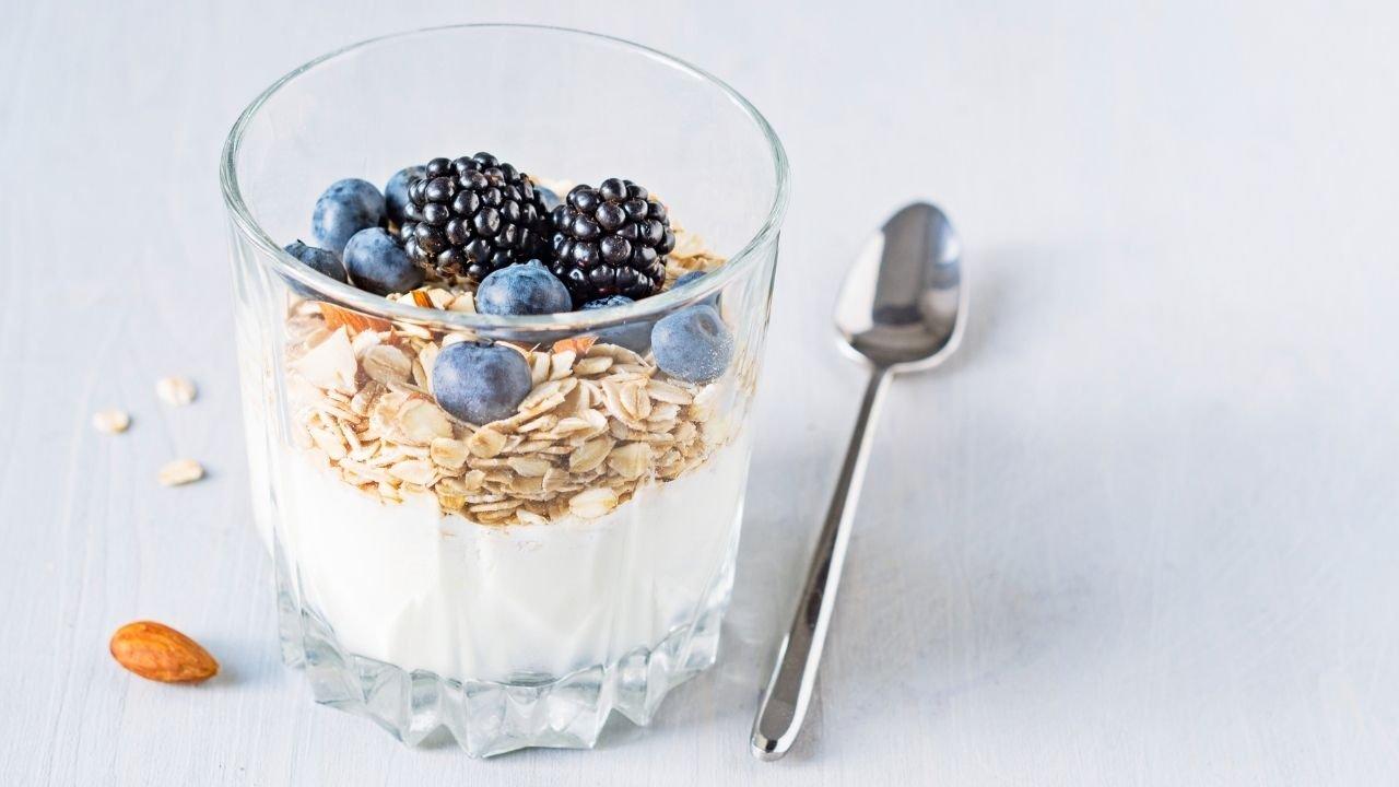 jogurt w przezroczystej szklance z płatkami górskimi, jeżynami i borówkami a obok leży łyżeczka