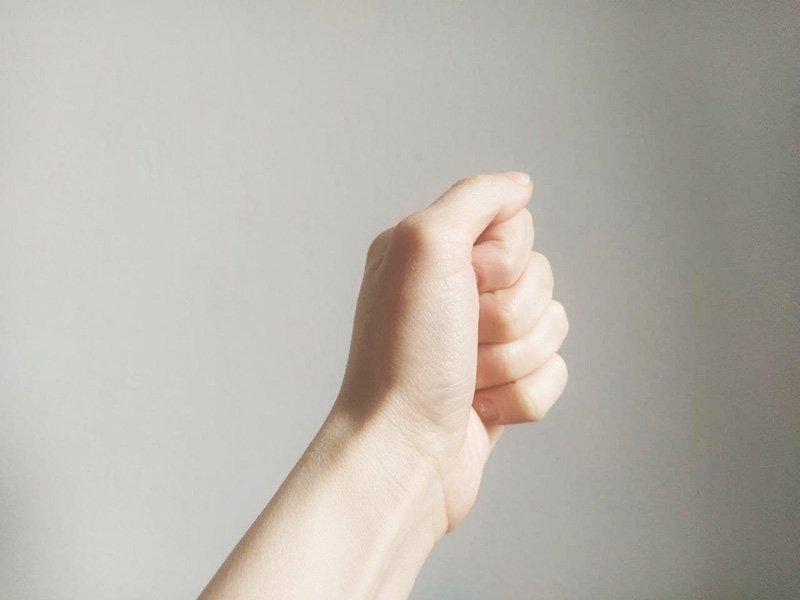 kobieca lewa dłoń ściśnięta na szarym tle