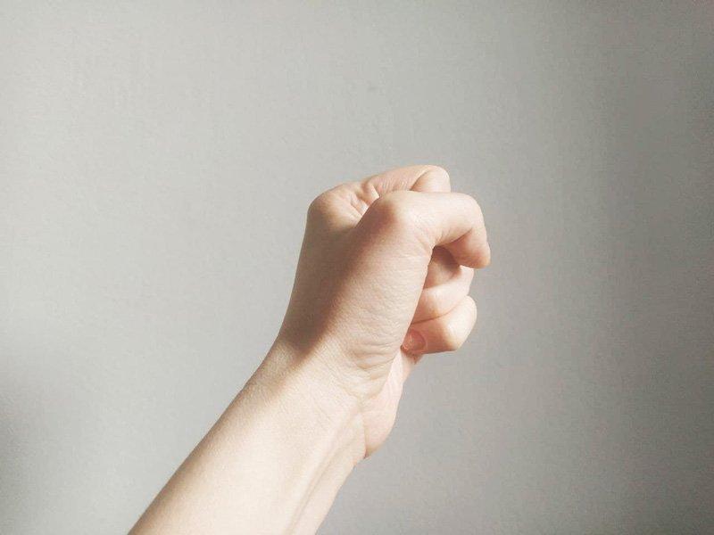 lewa kobieca dłoń na szarym tle