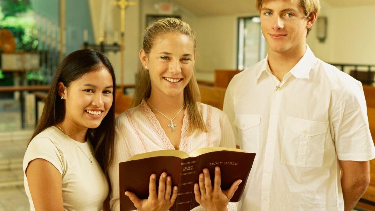 grupa uśmiechniętych młodych ludzi stoi w środku w kościele