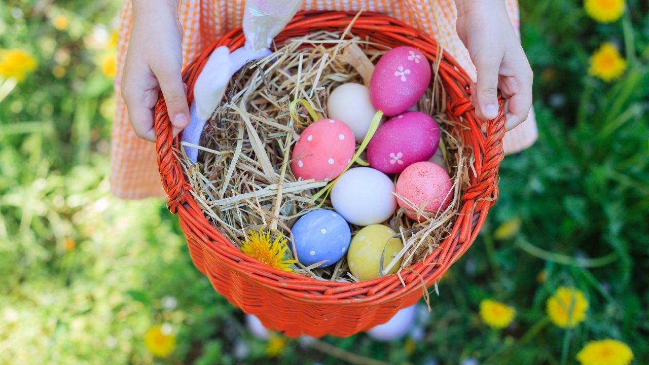 kolorowe jajka włożone do pomarańczowego koszyka trzymanego w dłoniach
