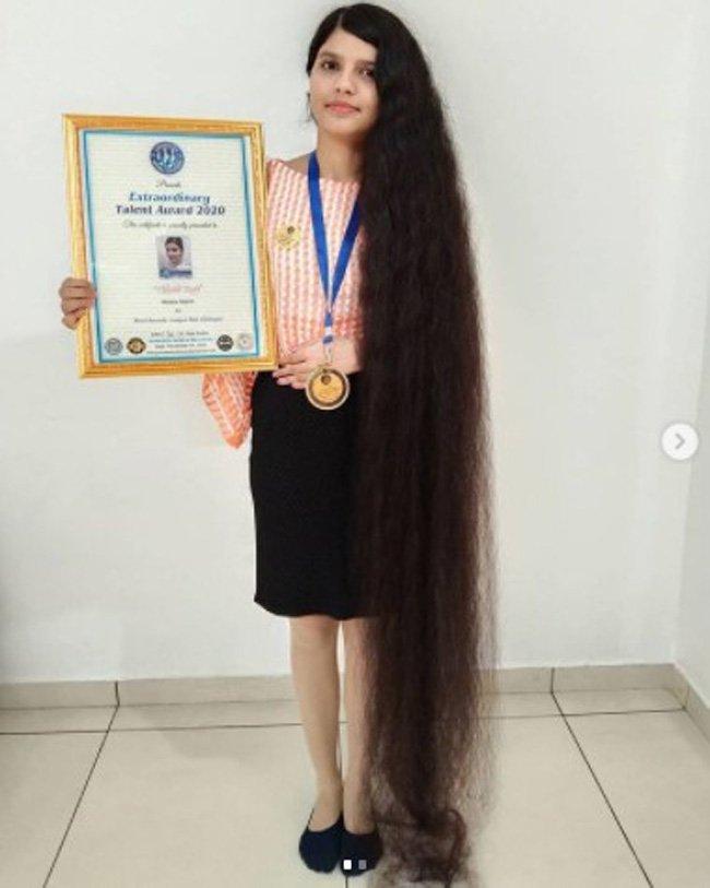 Dziewczyna z długimi włosami trzyma dyplom w dłoniach