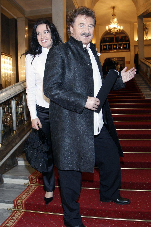 Ewa Krawczyk w białej koszuli stoi za uśmiechniętym Krzysztofem Krawczykiem na tle czerwonych schodów