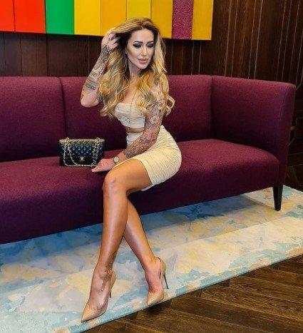 Sylwia Peretti w beżowej sukience siedzi na bordowej kanapie