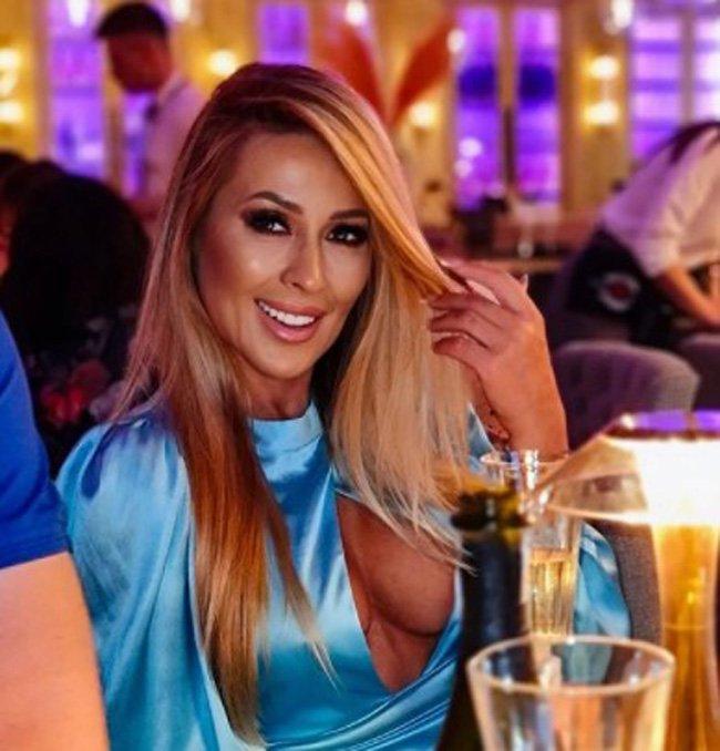 Sylwia Peretti w niebieskiej bluzce z ogromnym dekoltem i z rozpuszczonymi włosami