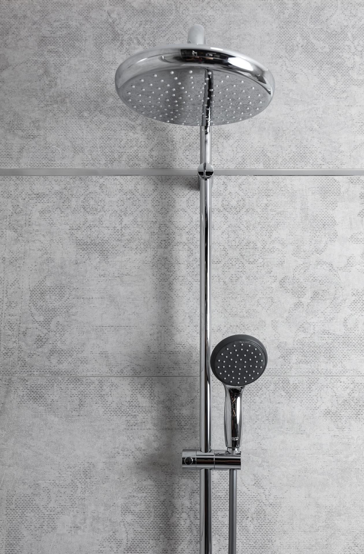 Srebrna bateria prysznicowa na tle szarej ściany łazienkowej