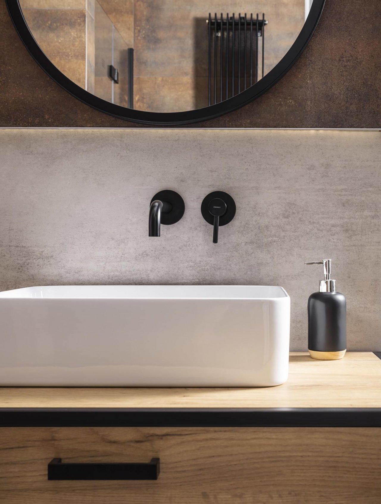 Widok łazienki z białą umywalką, okrągłym lustrem i czarnymi bateriami