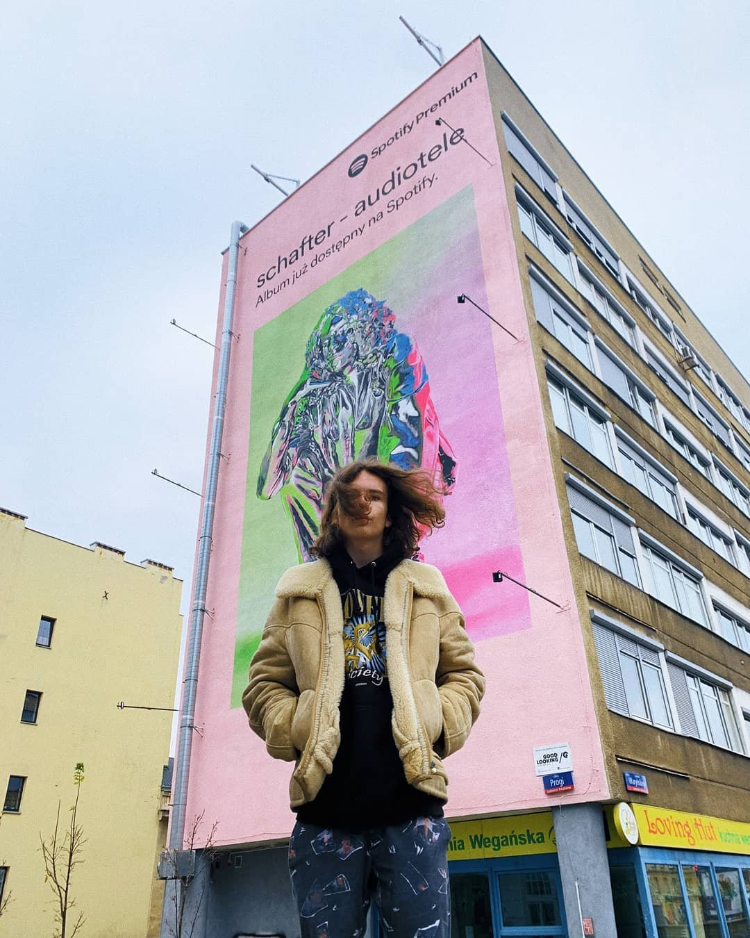 młody chłopak na tle bloku z muralem przedstawiającym okładkę jego płyty