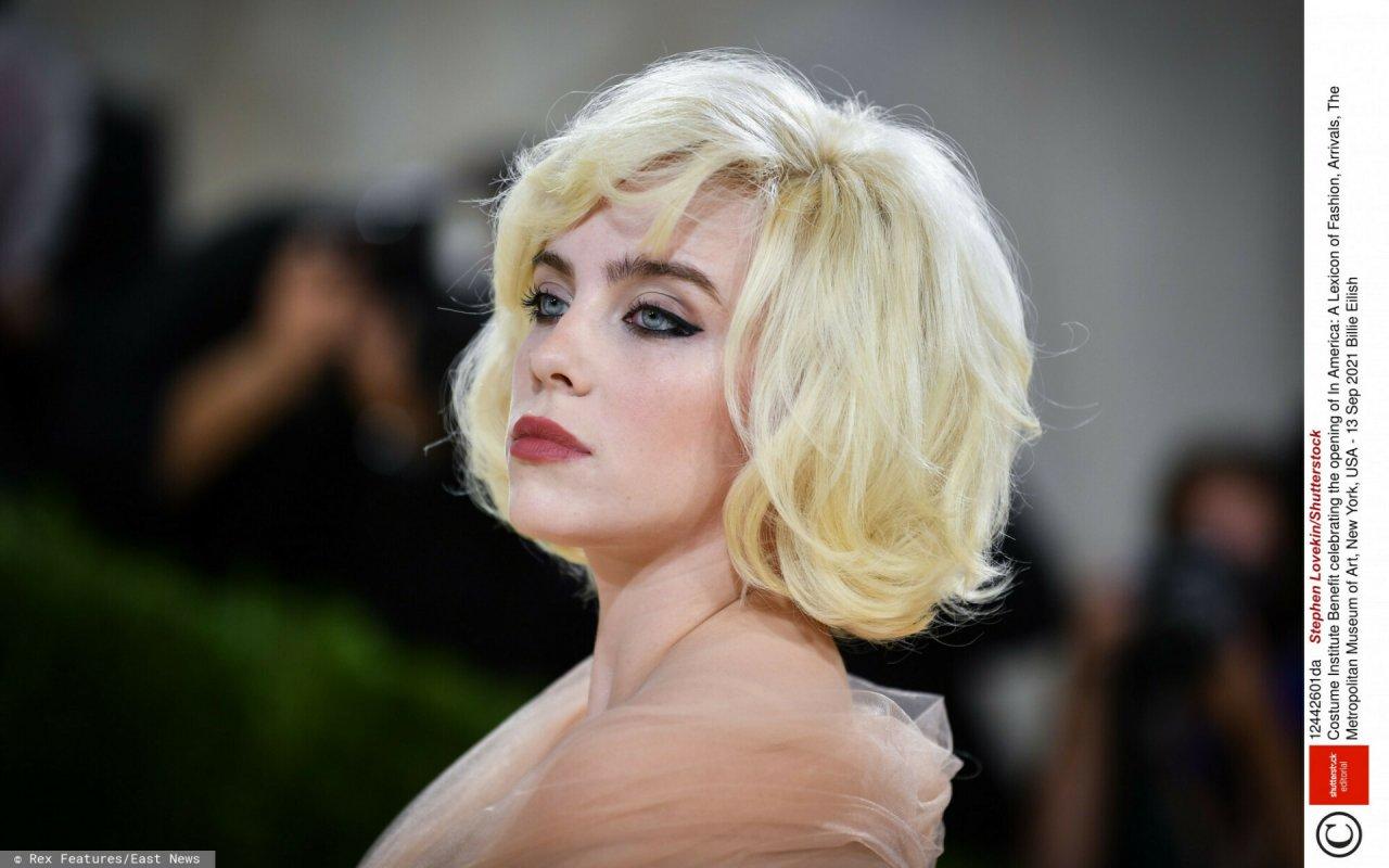 Zbliżenie na zamyśloną twarz Billie Eilish w blond włosach wystylizowanych na Marilyn Monroe