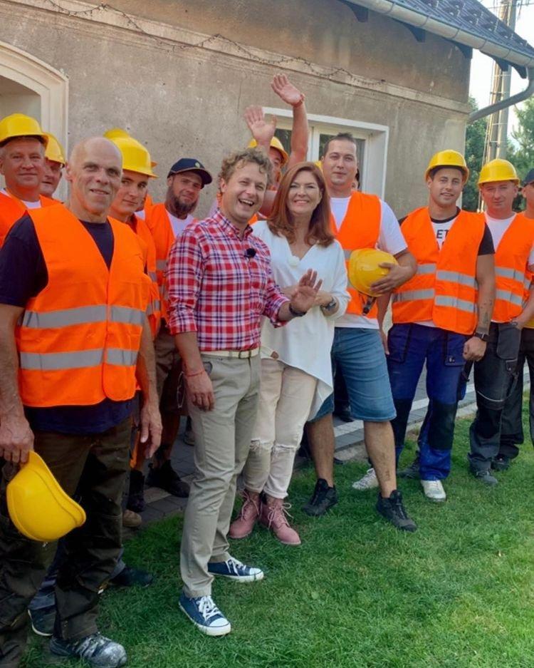 Katarzyna Dowbor pozuje z ekipą robotników z odblaskowych kamizelkach