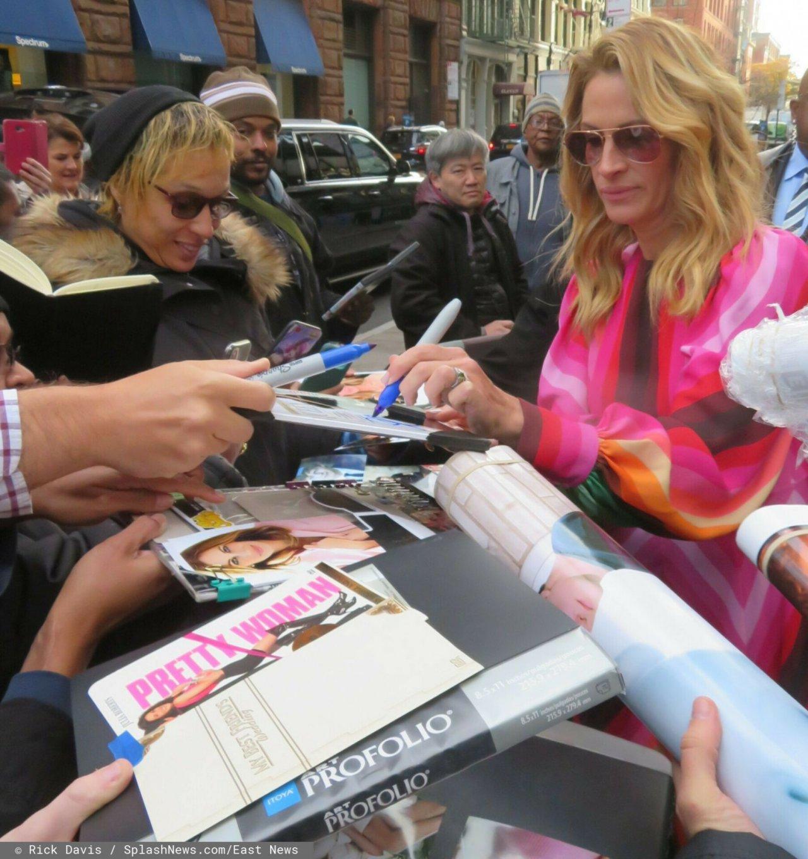 Julia Roberts rozdaje autografy w różowej kutrce.