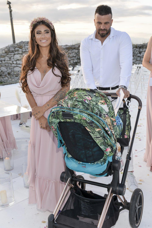 Maja Hyży w beżowej sukience i w wianku na głowie stoi obok partnera i wózka
