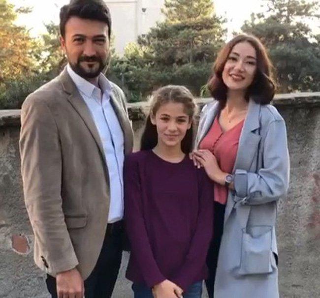 Ipek,i Omer uśmiechają się szeroko i stoją u boku małej dziewczynki