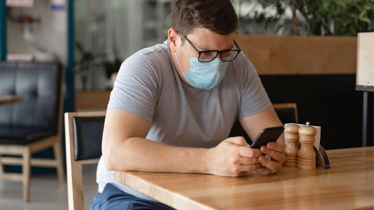 mężczyzna w okularach i maseczce siedzi przy stole i trzyma w dłoniach telefon