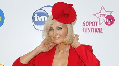 Szałowa Reni Jusis w czerwonym komplecie, z ozdobą na głowie i w platynowym blondzie na Festiwalu w Sopocie