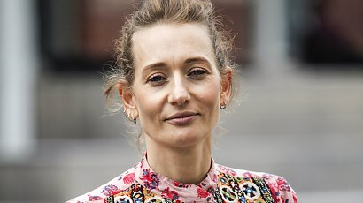 Rudowłosa Magdalena Popławska w różowym garniturze z satyny i trampkach. Nie do końca trafiona stylizacja...
