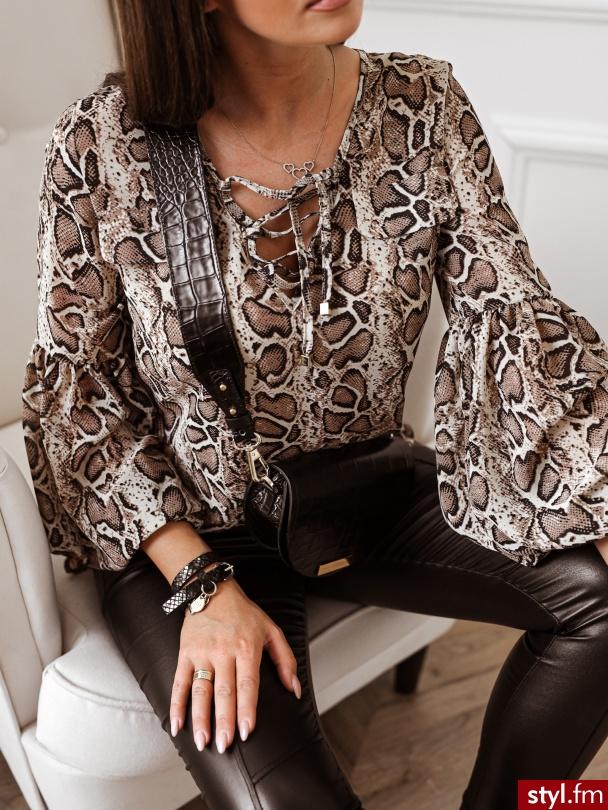 Bluzka wykonana jest z lekkiego materiału. Posiada wiązanie na biuście oraz długie bufiaste rękawy z poziomym przeszyciem. Tył bluzki jest delikatnie dłuższy. Bluzka w wężowy wzór idealnie sprawdzi się w wielu stylizacjach. - Bluzki Ciuchy Moda