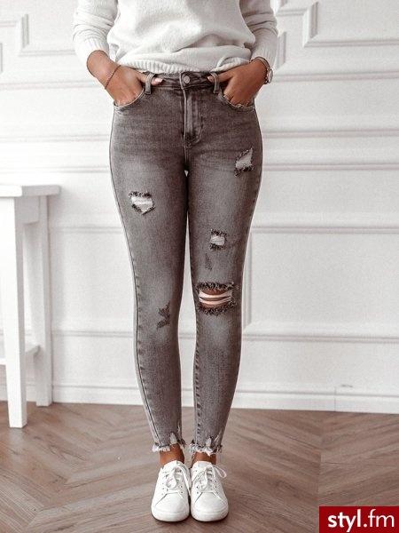 Spodnie wykonane zostały z szarego jeansu z modnymi obecnie przetarciami. Postrzępione nogawki nadają całości charakteru. Jest to idealny wybór do białej koszuli oraz butów w jasnym odcieniu. https://roseboutique.pl/ - Jeansy Spodnie Moda